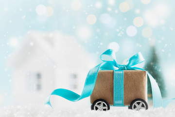 Christmas gift or present box on wheels against turquoise bokeh background. Holiday greeting card.
