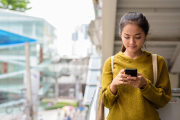 Young beautiful Asian woman using mobile phone in city