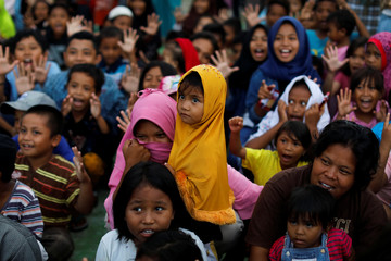 Children gather to receive occupational therapy at a camp for displaced victims of the earthquake and tsunami in Palu