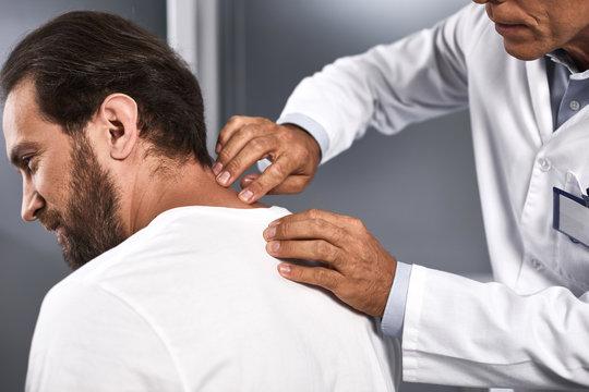 Medical advisor probing cervical vertebrae and identifying various pathologies of cervical spine