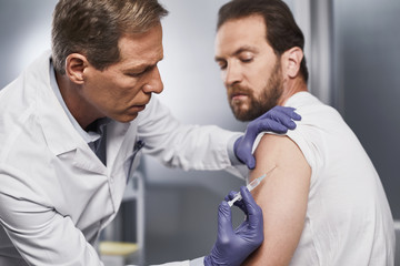 Adult doctor making intramuscular injection to male patient. This drug is necessary for treatment and further recovery