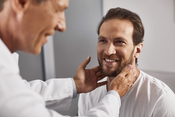Smiling doctor testing lymph nodes to checking their size and absence of inflammation of male patient