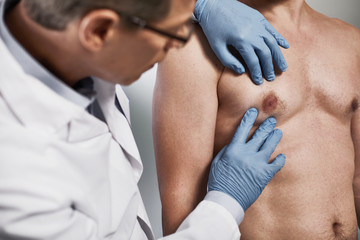 Close up of doctor conducting external examination and palpation of patient chest for finding various pathologies