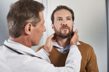 Waist up portrait of serious medical adviser checking of lymph nodes of male patient