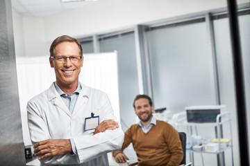 Waist up portrait of smiling medical adviser standing and holding arms crossed with male patient on background
