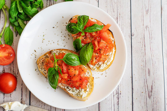 Traditional toasted Italian tomato bruschetta with spice and basil on light wooden background. Top view vith copy space
