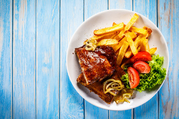 Grilled ribs, French fries and vegetables on wooden background