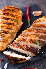 Grilled chicken fillets on slate plate on Gray concrete background. Healthy diet food concept, flat lay close up