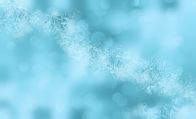 Winter shiny snowflakes blurred background in light blue pink colors. Blurry Christmas holiday background with snow flakes, frost pattern, soft flares of light. Copy space