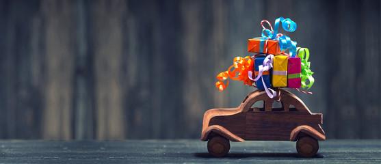 Holzauto mit bunten Geschenken