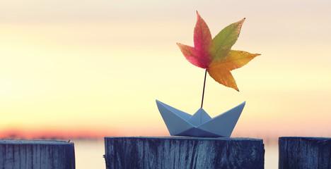 Papierboot mit bunten Laubblatt als Segel - Herbst