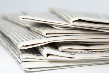 stacked newspapers on white background