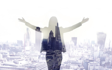 Young woman looking over the City of London at the early morning time. Future, new business opportunity and business success concept.