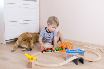 Three years old child boy playing with wooden toy railway at home in the children's room, shiba inu dog sitting near him. Freindship lifestyle concept