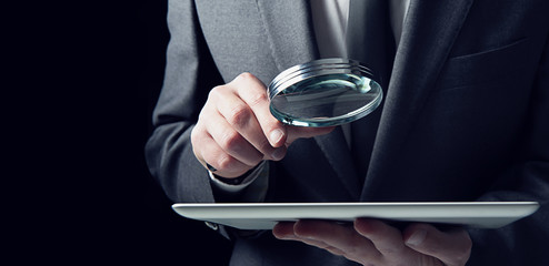 Businessman examines a tablet with a magnifying glass. Concept of internet security