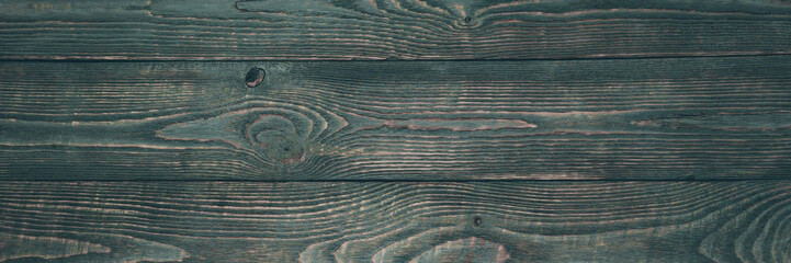 Background of wooden texture boards with remnants of dark green paint. Horizontal. Narrow.