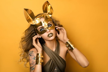Beautiful girl in fashionable golden leather rabbit mask on yellow background. Concept for party