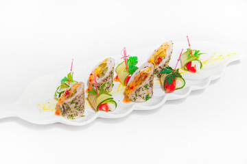 Vegetable rolls on a white plate. Cold snacks in the restaurant. Snack on skewers on a light background