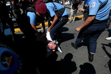 "Riot police try to detain a protester during a march called ""United for freedom"" against Nicaraguan President Daniel Ortega in Managua"