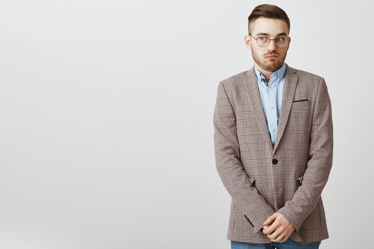 Intense worried european male employee feeling awkward and confused making mistake being scolded by boss feeling discomfort being in uncomfortable situation holding hands near pants and gazing aside