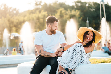 Handsome bearded man and his beautiful girl resting near fountains