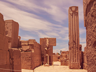 The ancient statue of the king (God or Pharaoh) and the stone column are surrounded by walls with hieroglyphs and ancient Egyptian symbols. Objects are located in Karnak Temple in Luxor, Egypt