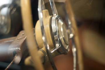 Blurred warm background - a fragment of the interior of a vintage car, focus on steering wheel detail