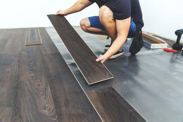 Obraz laminate flooring - worker installing new floor - fototapety do salonu