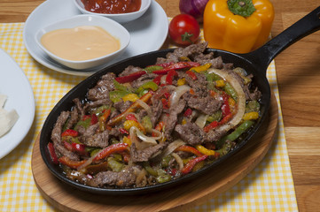 beef fajitas with colorful bell peppers in pan and sauces
