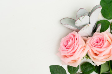 Rose fresh flowers with green leaves on table from above with copy space, flat lay scene