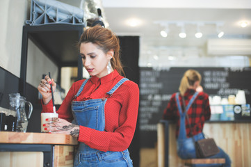 trendy young woman in red shirt and denim costume blending her coffee in bar