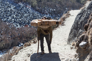 Nepalese porter carrying a heavy load to the pass in Nepal Himalaya