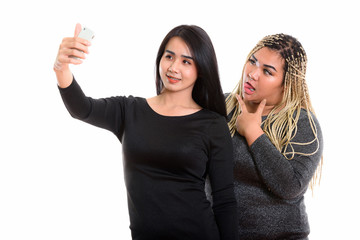 Young happy Asian transgender woman and fat Asian woman smiling