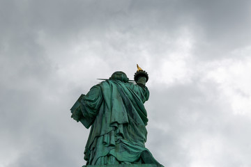 New York City / USA - AUG 22 2018: The statue of liberty back view in cloudy sky