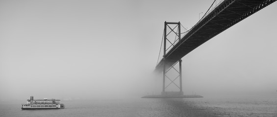 Ferry boat crossing under a suspension bridge in Halifax, Nova Scotia in thick fog.