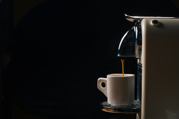 Coffee machine with capsule. Pouring coffee espresso over dark background, free copy space for your text