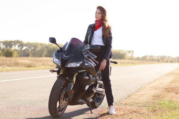 Transport and extreme concept. Thoughtful stylish female motorcyclist enjoys high speed, poses on fast bike, breathes fresh air, concentrated into distance, wears stylish black clothes for bikers