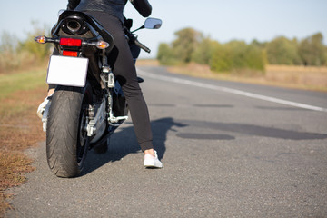 Cropped image of unrecognizable female bikes poses back on bike at asphalt, wears black clothes, blank copy space aside for your advertisement or promotional text. People, transport, destination