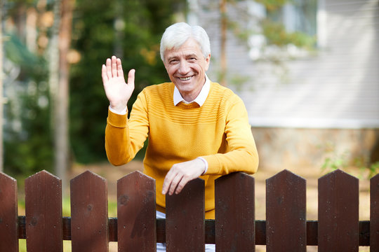 Cheerful senior man in casualwear standing by wooden fence and waving his hand to you