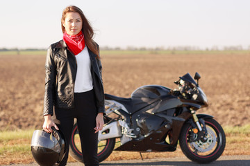 People, lifestyle, hobby, riding concept. Horizontal view of beautiful woman biker wears stylish clothes for motocyclists, carries helmet, participates in racing competitions, rides fast motorbike