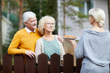 Mature woman giving her new neighbours homemade fresh apple pie on plate over fence Wall mural