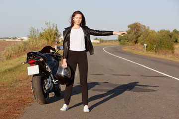 Horiontal shot of professional female biker stands near brocken motorbike, wears leather jacket, holds helmet, hitchhikes on roadside, asks for help. Problems with transport and travelling concept