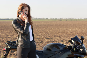 Female biker has phone conversation, stops on road, poses near motorbike, dicusses latest news with friend, dressed in leather jacket and black trousers. Technology and transportation concept