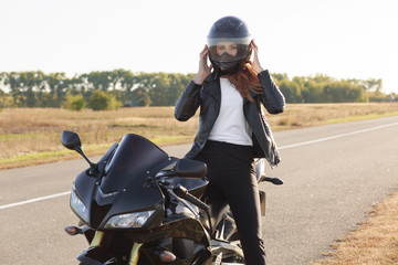 Horizontal view of stylish confident female biker dressed in fashionable clothes, sits on motorbike, wears helmet, covers long destination, poses outdoor. Motorcyclist enjoys outdoor travel.