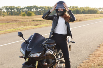 Photo of attractive female biker dressed in leather jacket, wears helmet, poses on motorbike against road background, likes her hobby, has rest for minute, has active rest. People, transport and speed Fototapete