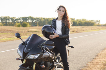 Pleasant looking woman has biker tour, poses on cool bike, holds helmet, wears leather jacket, likes extreme sport, likes driving. People, driving, active lifestyle concept. Biker traveles on morobike
