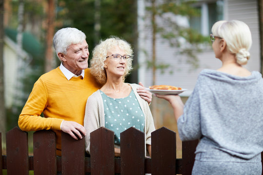 Mature woman giving her new neighbours homemade fresh apple pie on plate over fence