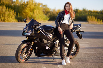 Photo of attractive woman has real adventure outdoor, stands near motorbike, dressed in bikers outfit, enjoys sunny day and calm atmosphere. People and motorcycling concept. Its time for ride