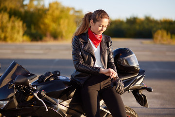 People, protection and driving concept. Pretty woman biker puts on protective gloves, helmet, prepares for driving on motorbike, poses against nature blurred background. People and speed concept