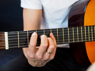 Male person playing acoustic guitar at closeup